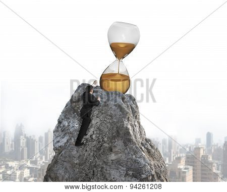 Businessman Trying To Grab Hourglass On Peak