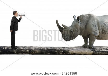 Businessman Using Speaker Yelling At Rhinoceros On Single Wooden Bridge