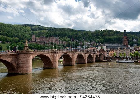 Historic Neuenheim Old Bridge in Heidelberg, Germany crossing the Neckar River with the ruins of the Heidelberg castle on the hillside overlooking the town