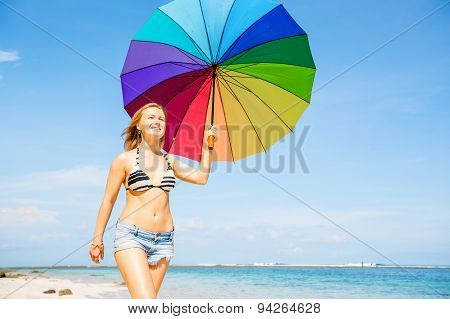 Young woman in blue shorts with colourful rainbow umbrella walking on beach