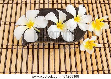 Tropical Plumeria On Bamboo Mat For Spa And Wellness Concept
