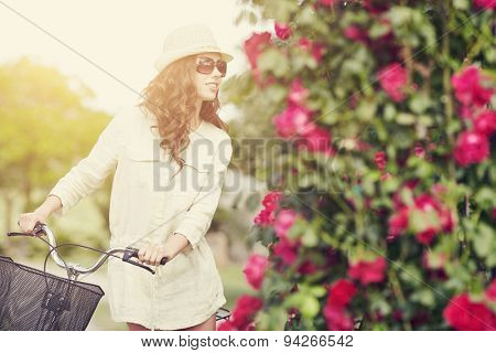 Woman with bike in Tuscany rose garden