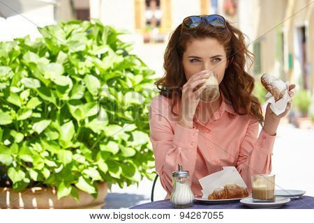 Portrait of beautiful blond woman sitting in outdoors cafe in Italy, drinking coffee and eating croissant.