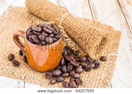 Coffee Cup And Coffee Beans With Burlap Sack  Background