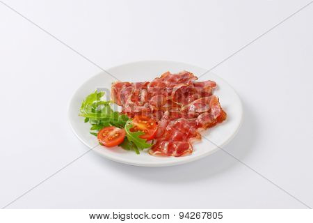 plate of fried bacon slices with garnish on white background