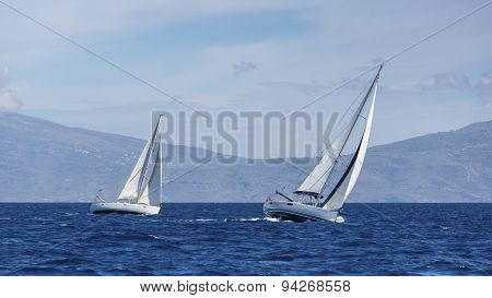 Boats in sailing regatta. Yacht sails with cloudless sky. Luxury yachts.