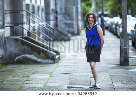 Smiling woman stands in the evening on a deserted street.