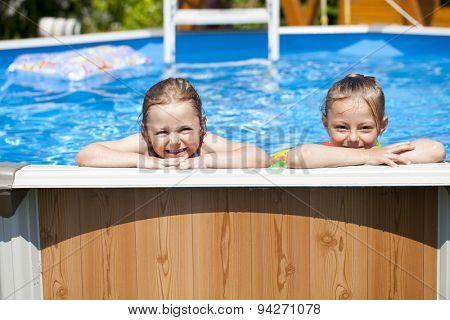 Two Happy sisters in bikini swimming pool