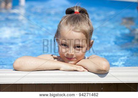 Happy little Girl in blue bikini swimming pool