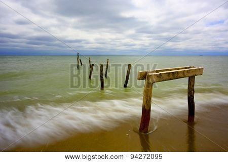 Piles of old wooden bridge on sea coast at evening time