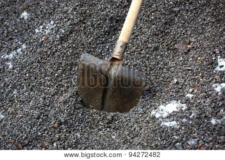 shovel with wooden handle in gravel