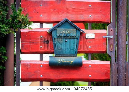 Abstract post box on red wooden gate