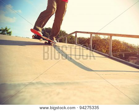 closeup of skateboarder legs skateboarding at skatepark ramp