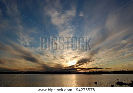 Sunset on a lake with scenic clouds.