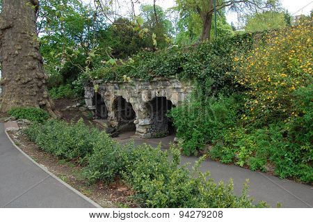 Old stone arches covered in greenery.