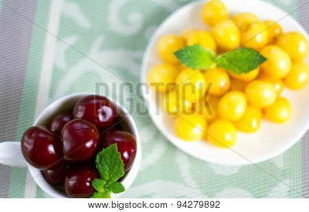 On A Cloth There Is A Saucer And A Cup With Sweet Cherries.