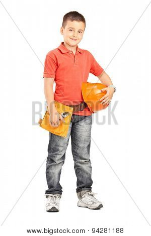 Full length portrait of a little boy holding a protective helmet and wearing a tool belt isolated on white background