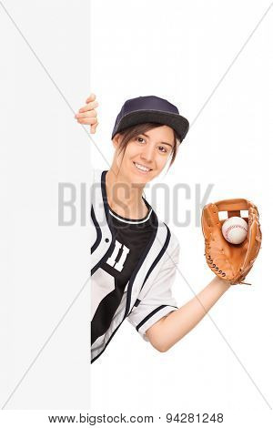 Vertical shot of a young woman in baseball jersey holding a baseball in a glove and posing behind a blank white signboard isolated on white background