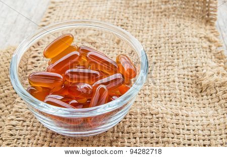 Fish Oil Capsules In Glass Bowl On Burlap Sack
