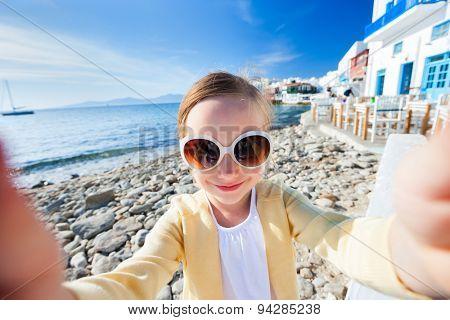 Cute little girl making selfieat Little Venice popular tourist area on Mykonos island, Greece