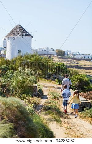 Back view of father and two kids walking towards traditional white windmill on Mykonos island, Greece, Europe
