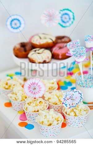 Donuts and other sweets on dessert table at kids birthday party