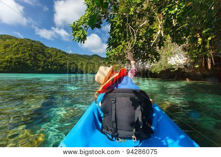 Little girl kayaking with her father in ocean among tropical islands during summer vacation