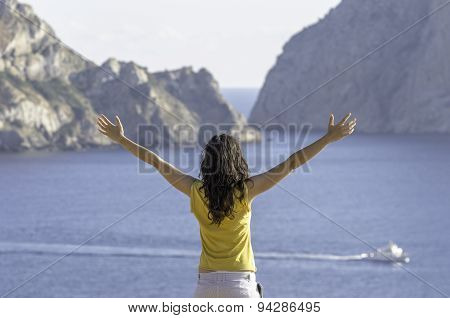 Young Happy Woman With Raised Hands And Looking The Sea.