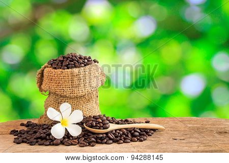 Coffee Beans In Burlap Sack On Wooden Table With Blurred Green Background