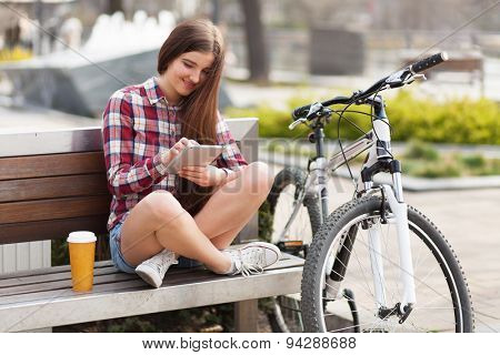 Young woman using a tablet pc in a park