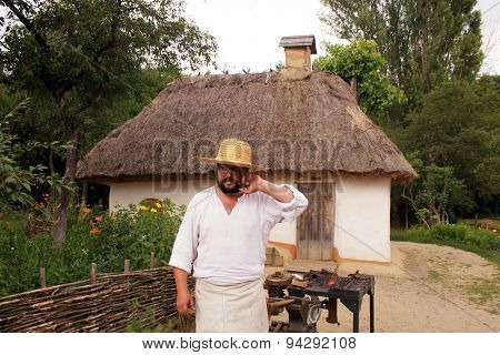 Local Ukrainian Man Near Traditional Rural House In Museum Pirogovo, Kiev, Ukraine