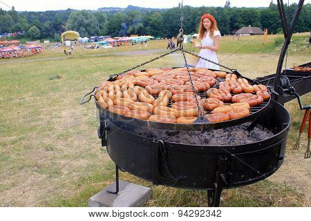 Cooking Traditional Sausages On Grill Outdoor Pan In Museum Pirogovo, Kiev, Ukraine
