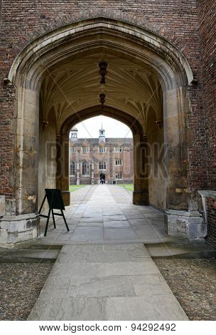 CAMBRIDGE, ENGLAND - MAY 13: View of Stone Path Through Archway to Historic Brick Building on Interior of Courtyard on Grounds of St Johns College, University of Cambridge, England on May 13, 2015