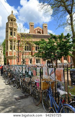 CAMBRIDGE, ENGLAND - MAY 13: Row of bicycles parked on the sidewalk along a wrought iron fence bordering an urban street in Cambridge, England with advertising posters on the railing on May 13, 2015