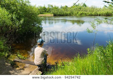 The Boy Catches Fish In The River On A Self Made Rod
