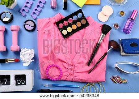Modern female clothing and accessories on color background