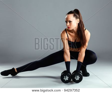 Athletic woman pumping up muscles with dumbbells and stretching legs .