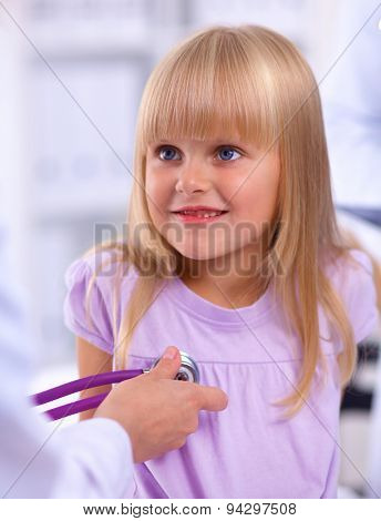 Female doctor examining child with stethoscope at surgery.