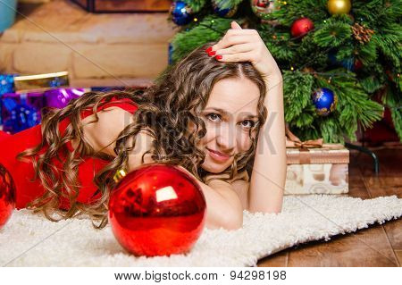 Girl Lies On A Rug At The Christmas Tree