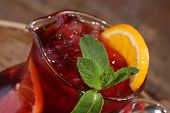 image of jug  - Wine of Sangrija with an orange in a transparent jug on a wooden table - JPG