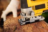 stock photo of sawing  - Carpenter is cutting wood with fret saw - JPG