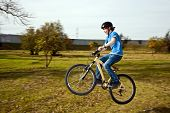 picture of dirt-bike  - boy jumps with his dirt bike over natural ramps in open area and enjoys racing  - JPG