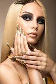 picture of nail-design  - Beautiful fashionable girl in a glamorous image with bright makeup and long gold nails - JPG