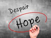 stock photo of hope  - Man Hand writing and choosing Hope instead of Despair with black marker on visual screen - JPG