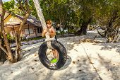 stock photo of tire swing  - boy climbinmg in a tire and swinging at the beach - JPG