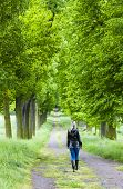 stock photo of woman boots  - woman wearing rubber boots walking in spring alley - JPG