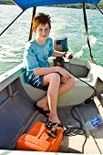 foto of outboard  - joung boy with red hair is steering the boat over the sea - JPG