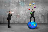 foto of juggling  - Boss using speaker yelling at businessman balancing on sphere juggling with currency symbol balls on business concepts doodles concrete wall background - JPG