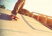 stock photo of skateboard  - closeup of skateboarder legs skateboarding at skatepark ramp - JPG