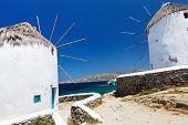 stock photo of greek-island  - White greek windmills overlooking Little Venice popular tourist destination at traditional village on Mykonos Island - JPG